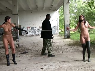 Two cute gals are punished close by an abandoned building by an ebony polished